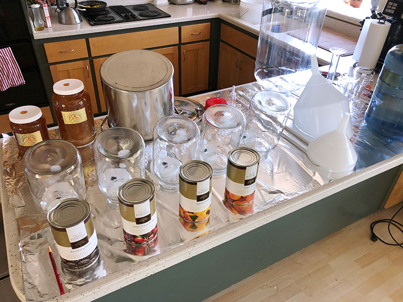An aluminum foil-topped kitchen counter is shown with various sizes of sterilized jars, funnels, pots and so on, along with two large jars of locally-produced honey and four jars of canned fruit purees. A five gallon jug of water water also sits on the counter.